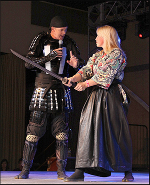 Samurai Dan is a tall man in a skull cap and black samurai-style armor.  He holds a microphone and holds his other hand demonstratively in front of Jillian who wears kimono and hakama and holds a katana.