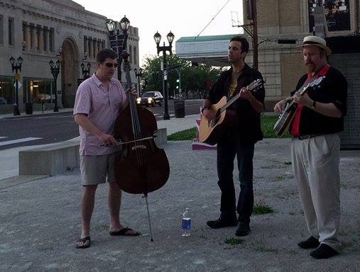 Three men stand on a street corner.  One plays an upright base, one plays an acoustic guitar, and the last plays a banjo.