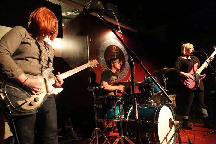 a redhead rocks out in the foreground while her other band members look fierce on a small bar stage